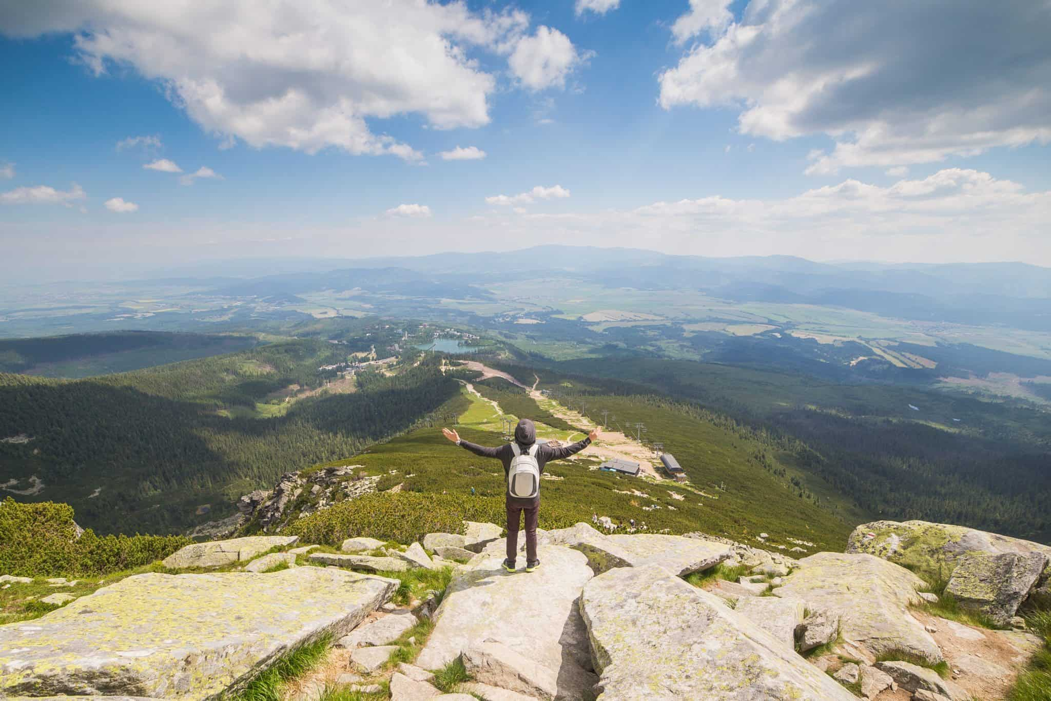 Picture of a man on the top of a hill embracing the world. An illustration in an article about finding the right marketing path.