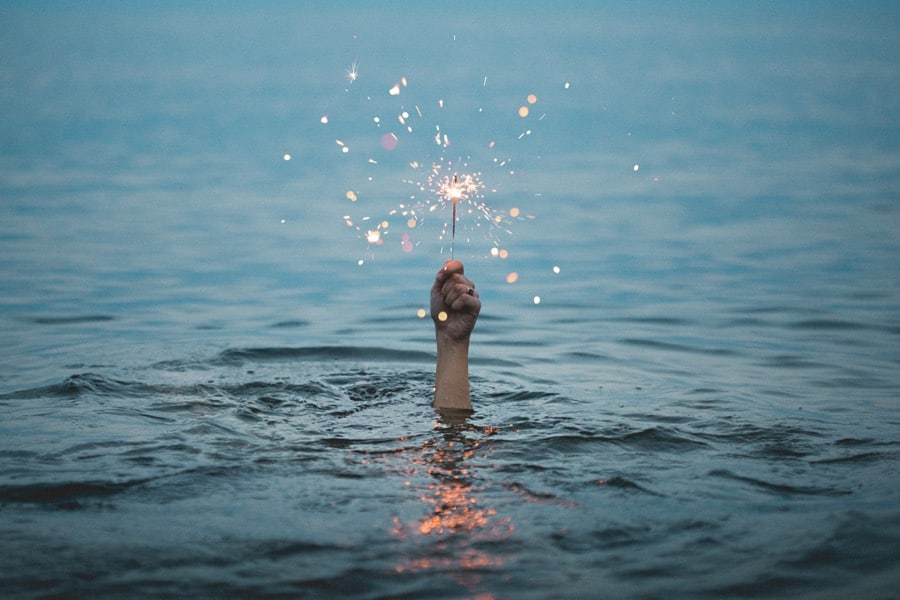 person under the sea holding a sparkler above water for and seo innovations article illustration