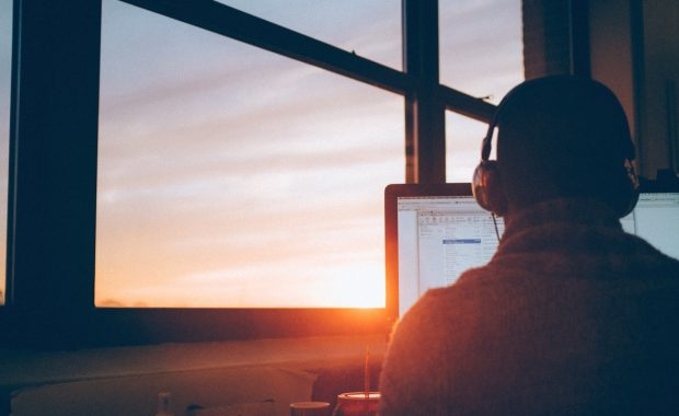 A digital marketer with headphones and a sunset out of the window